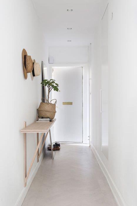 Белая прихожая с минимальном количеством мебели и аксессуаров
